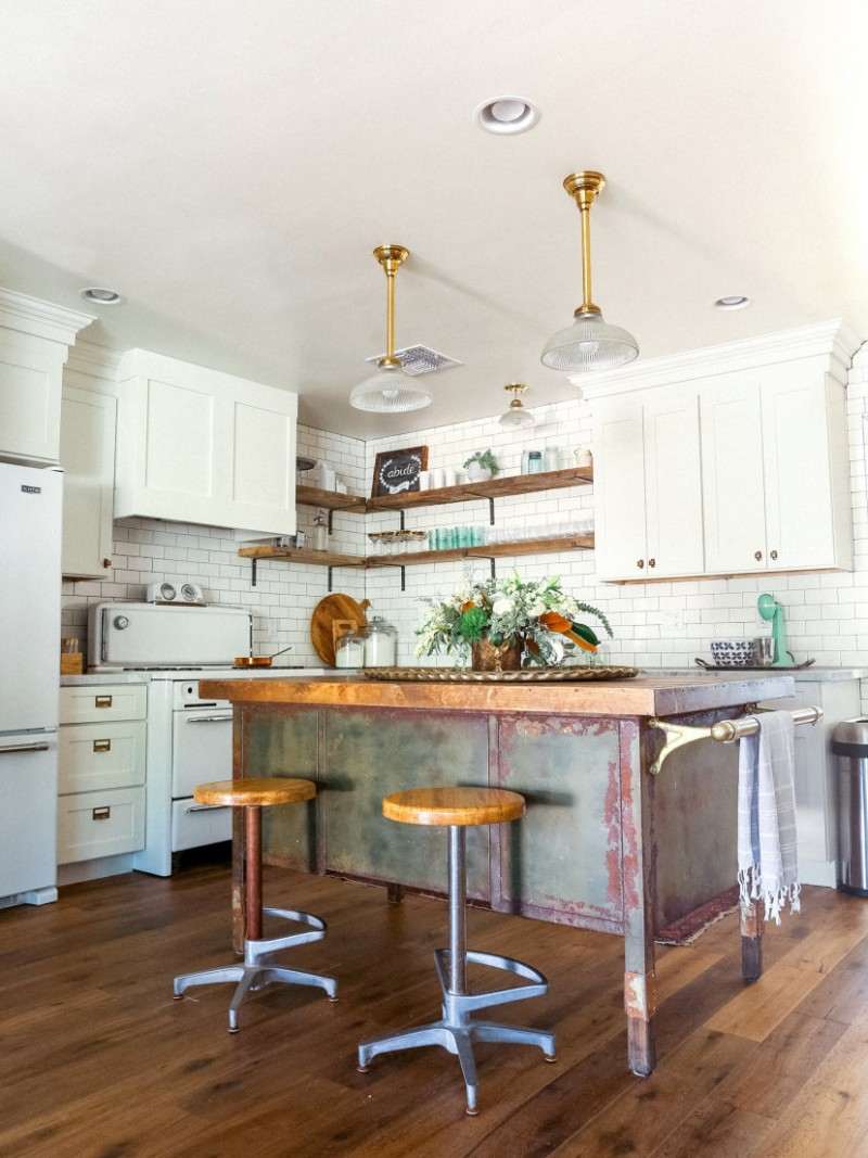 eclectic kitchen set shabby prep table with butcher block surface round wood top stools white kitchen cabinetry white subway tile walls & backsplash wood pallet floors