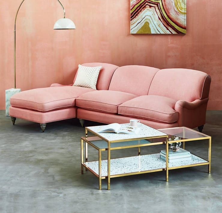 framed terrazzo coffee table with gold toned frames and tempered glass surface sweet pink couch with facing chaise addition