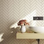 Herringbone Tile Walls In Broken White Color Potted Flowers Light Wood Bathroom Counter Vanity With White Sink