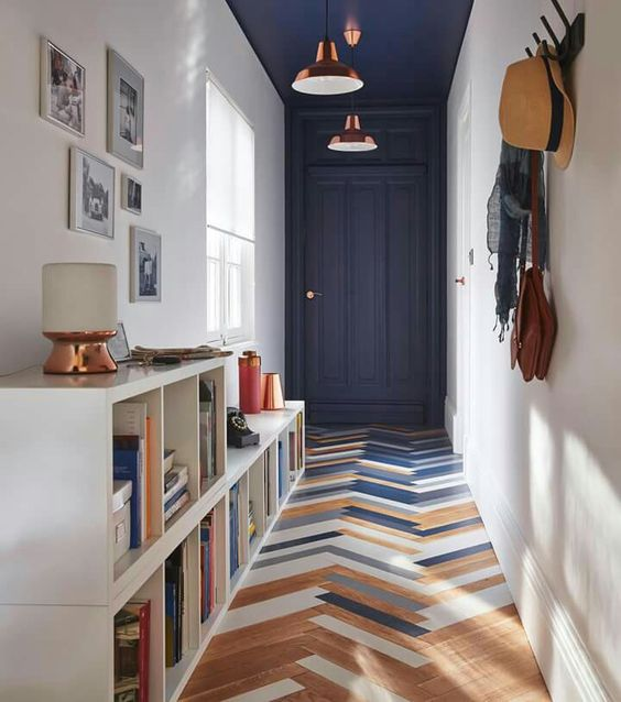 herringbone tiles in three colors floor book shelves in white navy blue door white walls