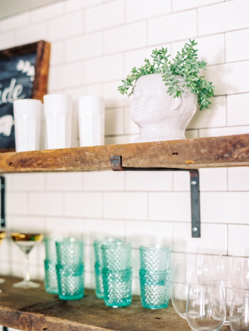 industrial open shelving unit with hard metal supports some decorative glasses