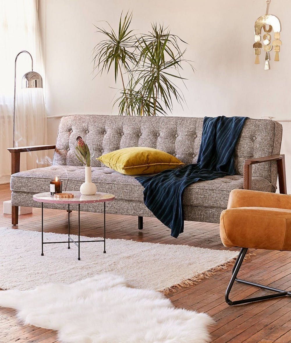 midcentury futon couch with tufted fabric cover in gray and wood frame white fabric rug wood floors