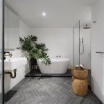 Modern Minimalist Bathroom Design Modern White Bathtub Medium Size Houseplant On Pot Gray Herringbone Tile Floors Wall Mounted Sink In White Wooden Stool
