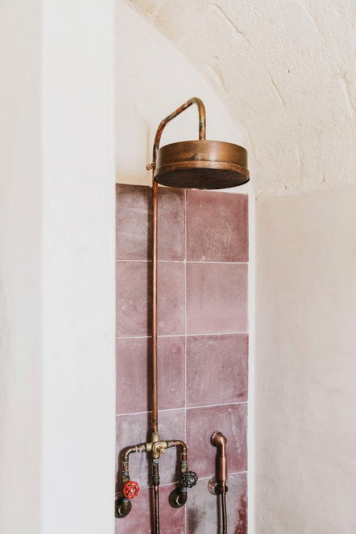 pink subway tile wall copper piping system with shower head concrete walls
