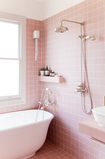 pink tile walls with white border lines white bathtub white bathroom sink stainless steel shower fixtures