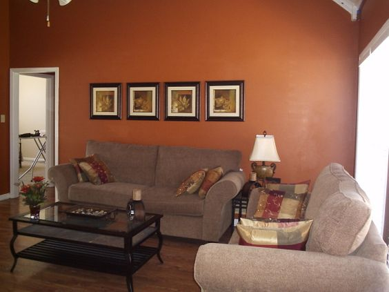 rusty orange wall paint gray sofas black coffee table wood floors
