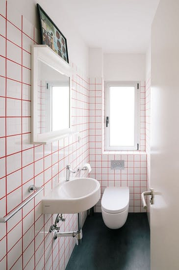 white tile walls with accent grout wall mounted sink in white wall mounted toilet in white black concrete floors