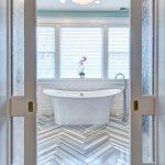 Wooden Herringbone Patterned Floors White Subway Tile Walls Classic Bathtub In White Standing Shower Faucet