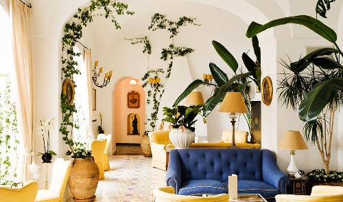 Italian style open concept living room tufted sofa in navy blue patterned tile floors decorative vines higher houseplants
