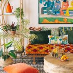 Boho Style Sofa With Multicolored Throw Pillows Wood Moroccan Style Table With Round Top Gray White Area Rug With Patterns Orange Floor Pillow Potted Houseplants