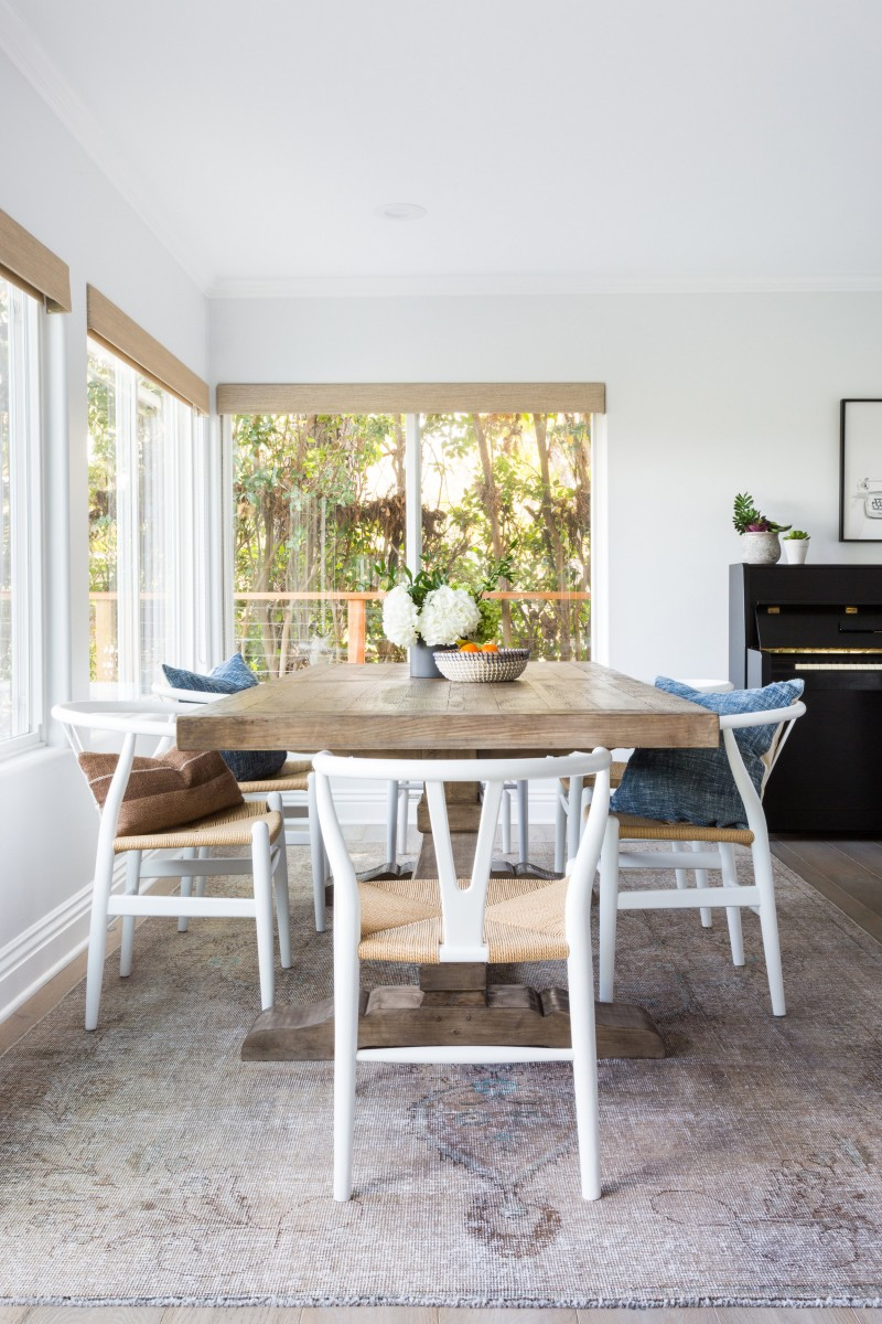 breakfast nook white structure dining chairs with woven surface seat butcher block dining table large glass windows
