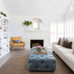 Bright Living Room Design Recessed Cabinets In White Leather Side In Light Caramel Modern Fireplace With White Brick Mantel Gold Frame Wall Mirror Clean White Sofa Tufted Ottoman Table In Matte Blue