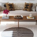 Broken White Sofa With Lower Profile And Wider Armrests Multicolored Throw Pillows Modern Wooden Coffee Table In Midcentury Modern Style White Area Rug With Centered Circle Pattern