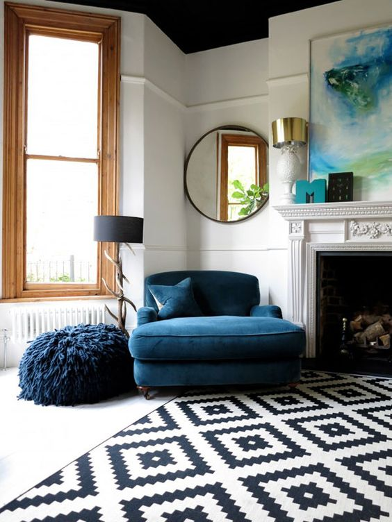 classic loveseat in navy blue fury pouch in navy blue black white area rug in modern patterns black framed wall mirror in circle shape
