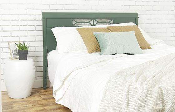 dard hunter green headboard white brick walls vase like bedside table wood floors