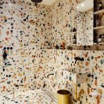 Full Terrazzo Master Bathroom Gold Toned Trash Bin Terrazzo Sink Gold Toned Piping System Clear Glass Door Black Finishing Ceiling Showerhead