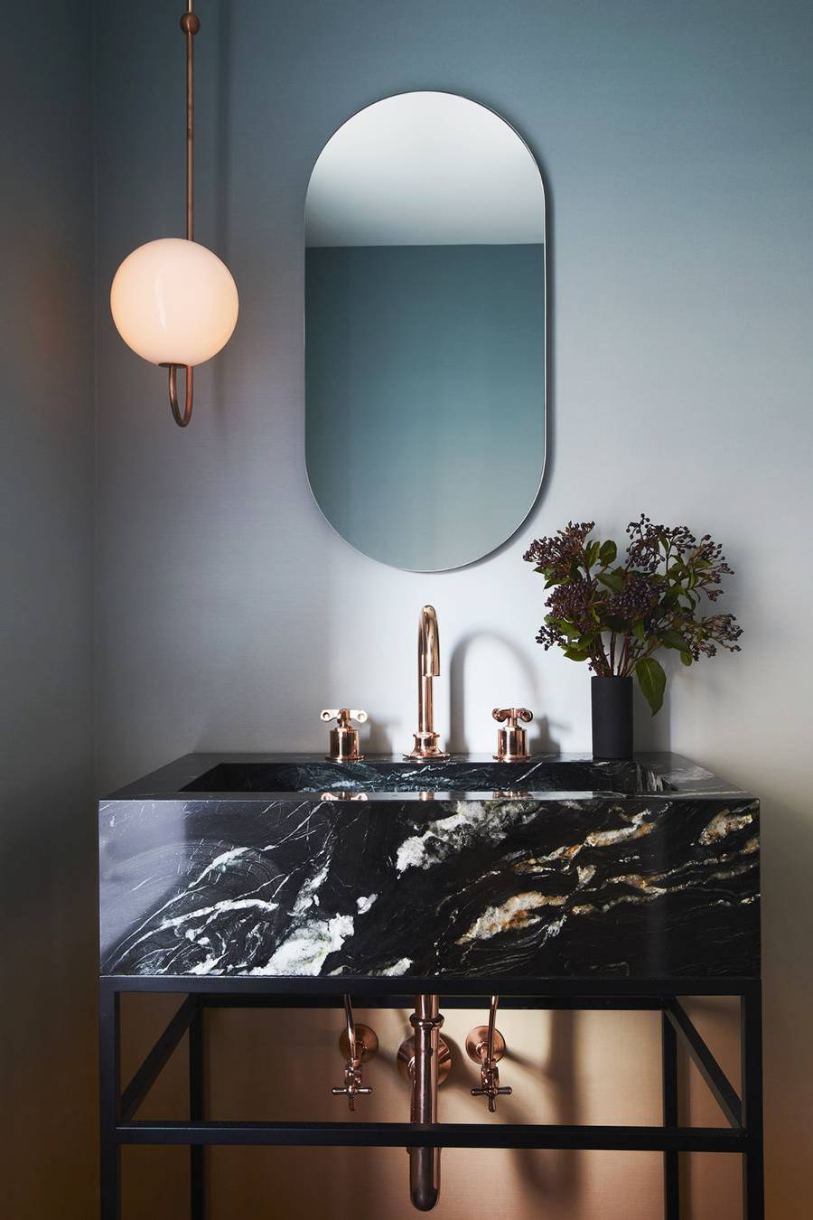 lower drop pendant with gold toned support frameless mirror black marble bathroom vanity gold toned faucet and piping