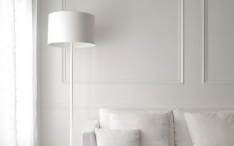 purely white walls lower base sofa in white white throw pillows white floor lamp muted black floors