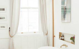 quirky bathroom design longer curtains with tiedback rope glass pendant light sleek bathtub in white geometric tile floor accent on light wood floors modern artwork