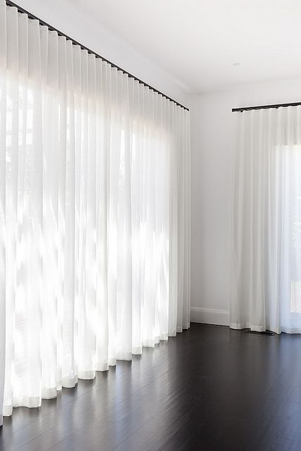 sheer curtains in white dark wood board floors purely white walls