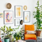 Small Boho Chic Living Room Brightly Orange Chair With Colorful Throw Pillow Woven Coffee Table Potted Houseplants Framed Wall Arts