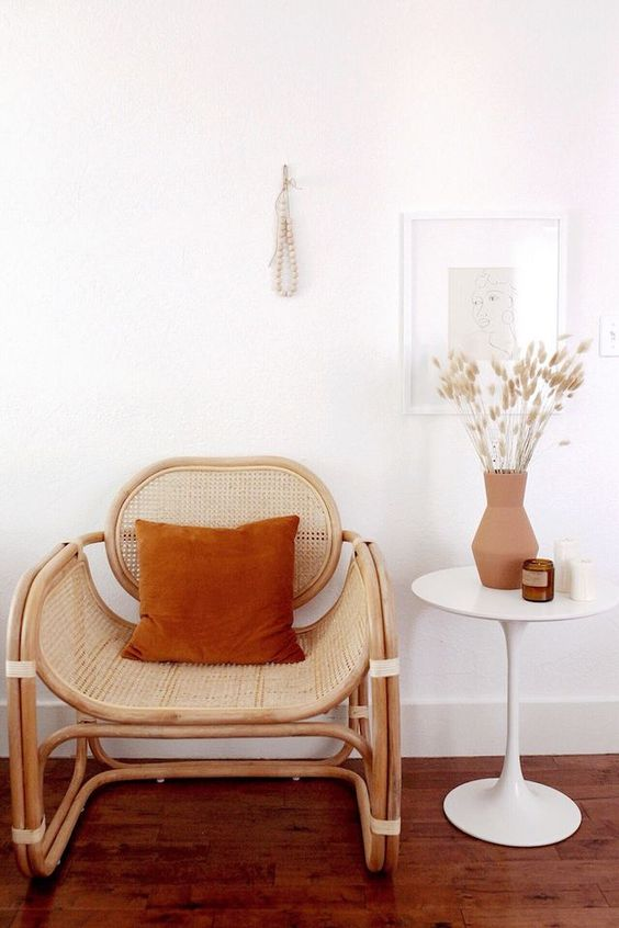 small seating area wooden chair with hand woven details sepia colored throw pillow round top side table in white small clay burnt vase for drying flowers