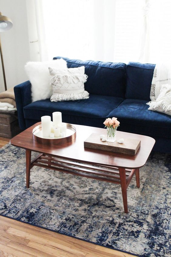 velvet covered sofa in navy blue white throw pillows hardwood coffee table in midcentury modern style blue washed area rug wood floors
