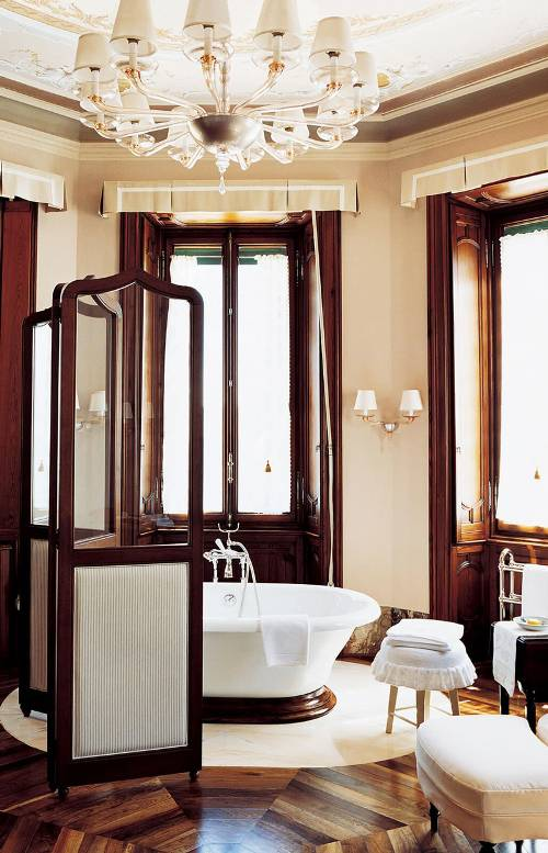 warm feel Italian bathroom bathtub in white Italian glass chandelier wood floors traditional room divider made of wood and glass