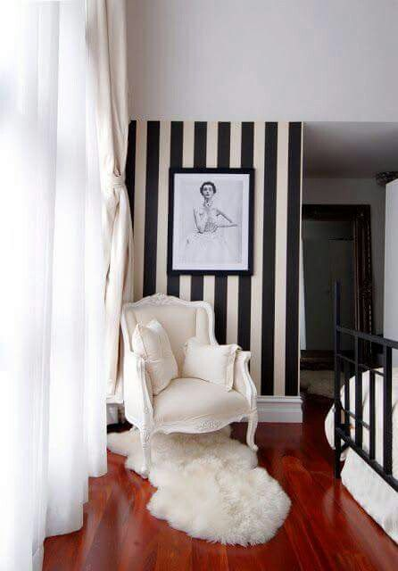 Medieval chair in white striped wallpaper in black white white shag rug darker wood floors