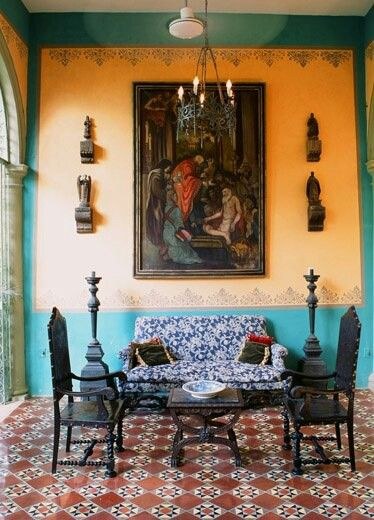 Medieval living room idea orange wall painting with Moroccan details on top black wrought iron chairs in Medieval style multicolored sofa textural color area rug