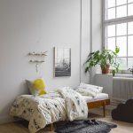 Scandinavian Style Teen Bedroom Idea Wood Bed Frame In Midcentury Modern Style White Walls Large Glass Window Light Wood Floors Black Fur Bedroom Mat