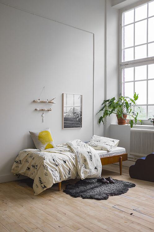Scandinavian style teen bedroom idea wood bed frame in midcentury modern style white walls large glass window light wood floors black fur bedroom mat