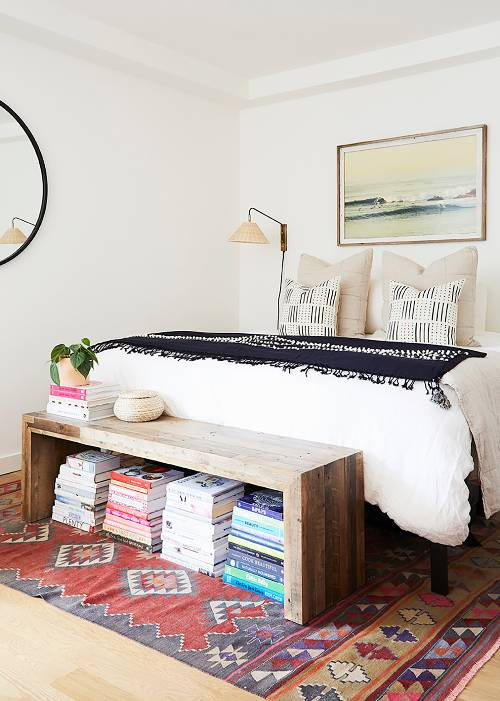 airy and soft bedroom textural color pillowcases white bedding treatment hardwood bench bed with under piles of books textural & colorful area rug