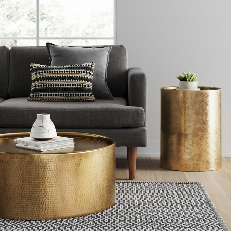 brass drum like coffee table deep gray sofa black white area rug brass side table with round top and base