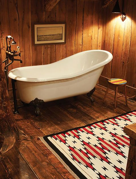 clawfoot bathtub in white multicolored area rug rainbow stool spotlight fixtures wood walls and floors