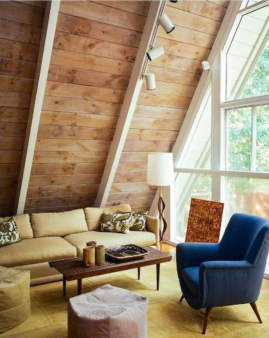 clean lines and modern cabin's living room idea modern sofa in light beige deep blue armchair in midcentury modern style light wood vaulted ceiling some spotlight fixtures huge glass window with big trims