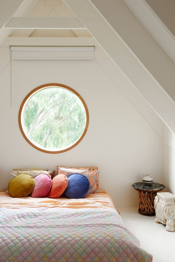coastal style bedroom with modern glams textured comforter soft orange bed linen colorful throw pillows corner side table with round top crispy white wall painted round wood framed glass window in center