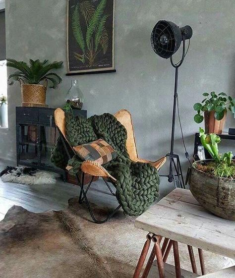 concrete like wall painting leather chair with hairpin legs knitted throw blanket in green cowhide area rug
