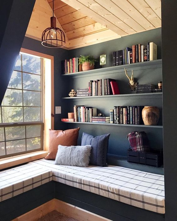 dark interior reading nook wall bookshelves L shaped bench seat with striped linen cover colorful throw pillows