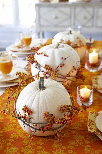 decorative white pumpkins with strings of dried small fruits clear glass for candles mustard table cover with flower prints