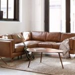 Drop Leaf Coffee Table Made Of Walnut Leather Sofa In Earthy Brown Woven Area Rug Wood Tripod Lamp