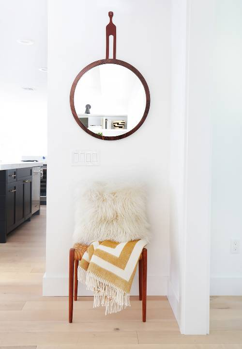 empty feel hallway with round decorative wall mirror chair with shaggy fur throw pillow throw blanket
