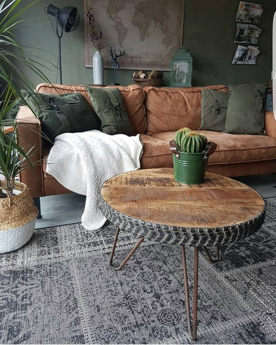 industrial look living room non gloss gray wall leather couch army green throw pillows round top coffee table with hairpin legs dark area rug natural fiber woven pot with houseplant