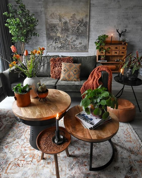 jungle warmer feel living room in gray modern velvet couch in gray round top wood coffee tables clay burnt additional table with round top potted houseplants wood drawing system gray tiled walls