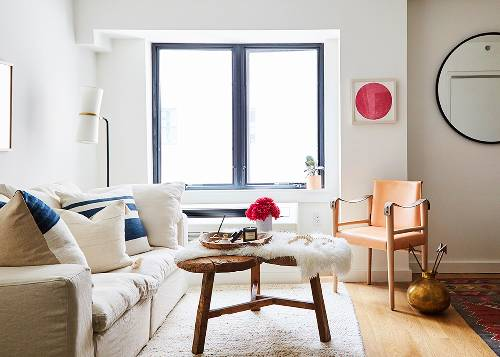 living room design white sofa with layers of throw pillows orange leather chair bright pink painting wood coffee table with white shag cover white area rug