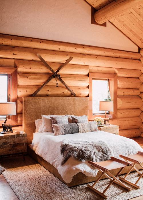 log wall bedroom idea wood grained bed frame with headboard white bedding with pile of pillows foldable x base bed benches light tone area rug