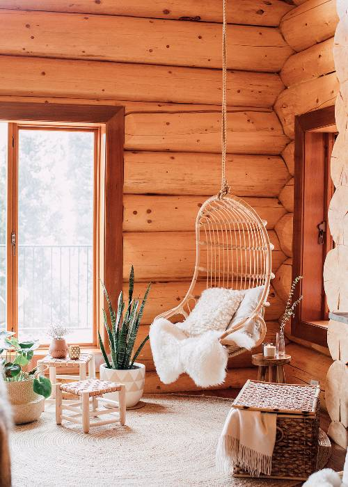 log wall cabin hanging rattan chair light wood stool with woven detail sheepskin area rug in white white throw pillows woven basket potted greenerys