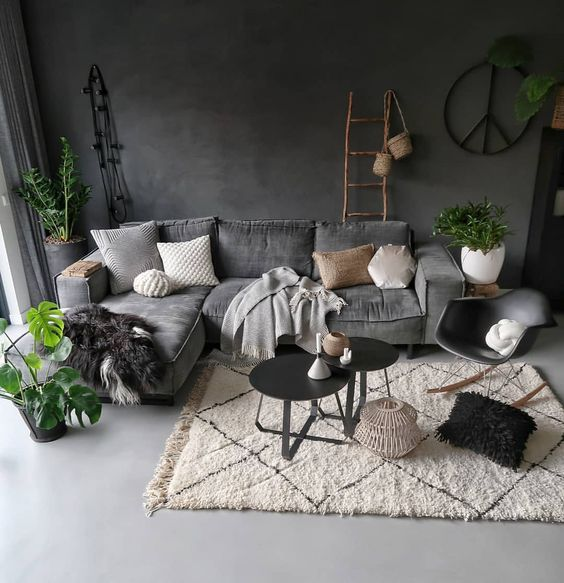 medium dark living room with Scandinavian touch modern velvet couch in gray light gray throw blanket white shag rug round top coffee tables in black light wood ladder rack