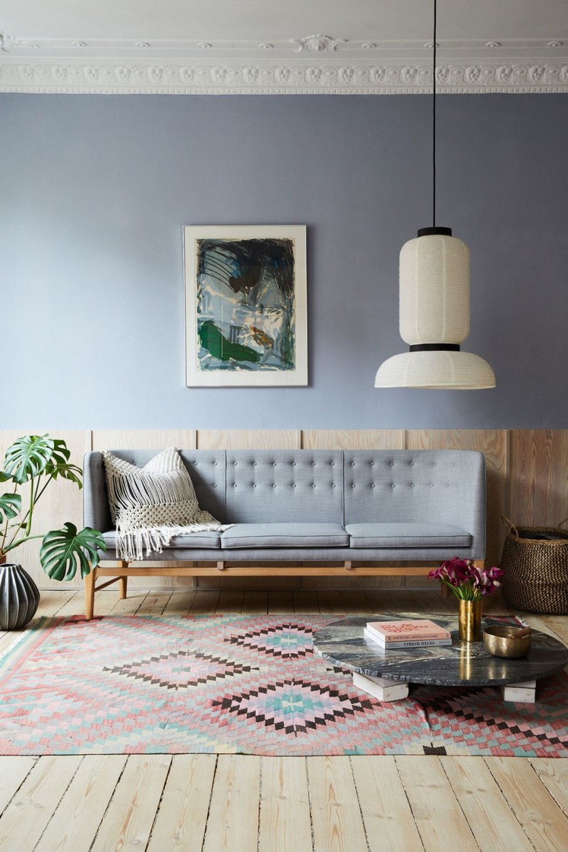midcentury modern sofa in light gray bohemian area rug floor marble coffee table with books base light wood floors white pendant potted houseplant