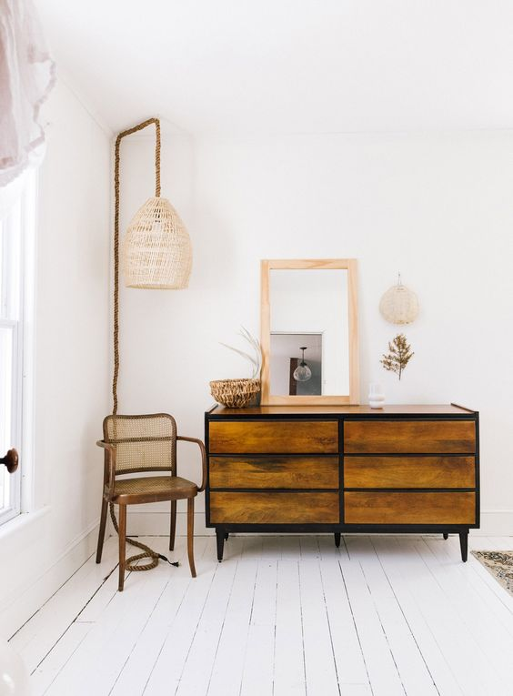 midcentury modern wood dresser with black frame midcentury modern wood chair wood framed leaning mirror corner pendant with cage like lampshade